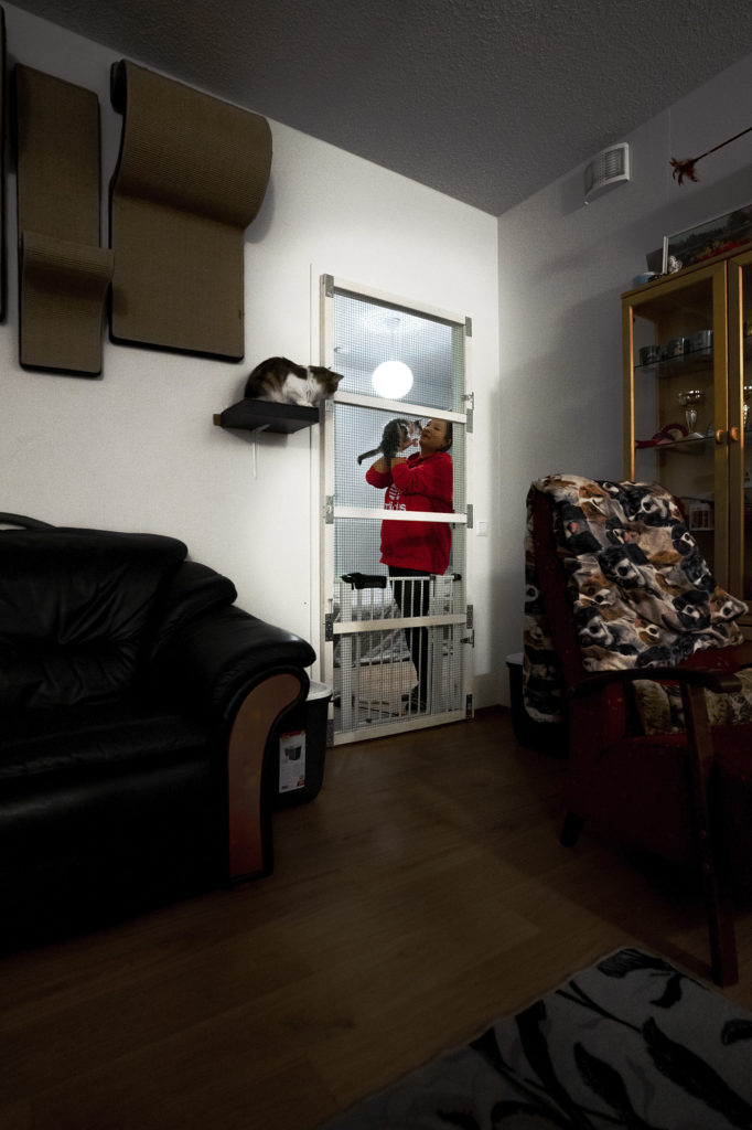 Henkilö pitää kissaa sylissä verkkoaidalla varustetun oven takana