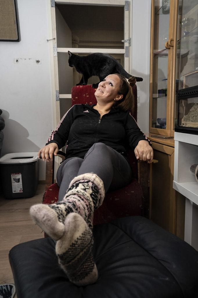Henkilö istuu nojatuolissa, musta kissa kävelee selkänojan päällä