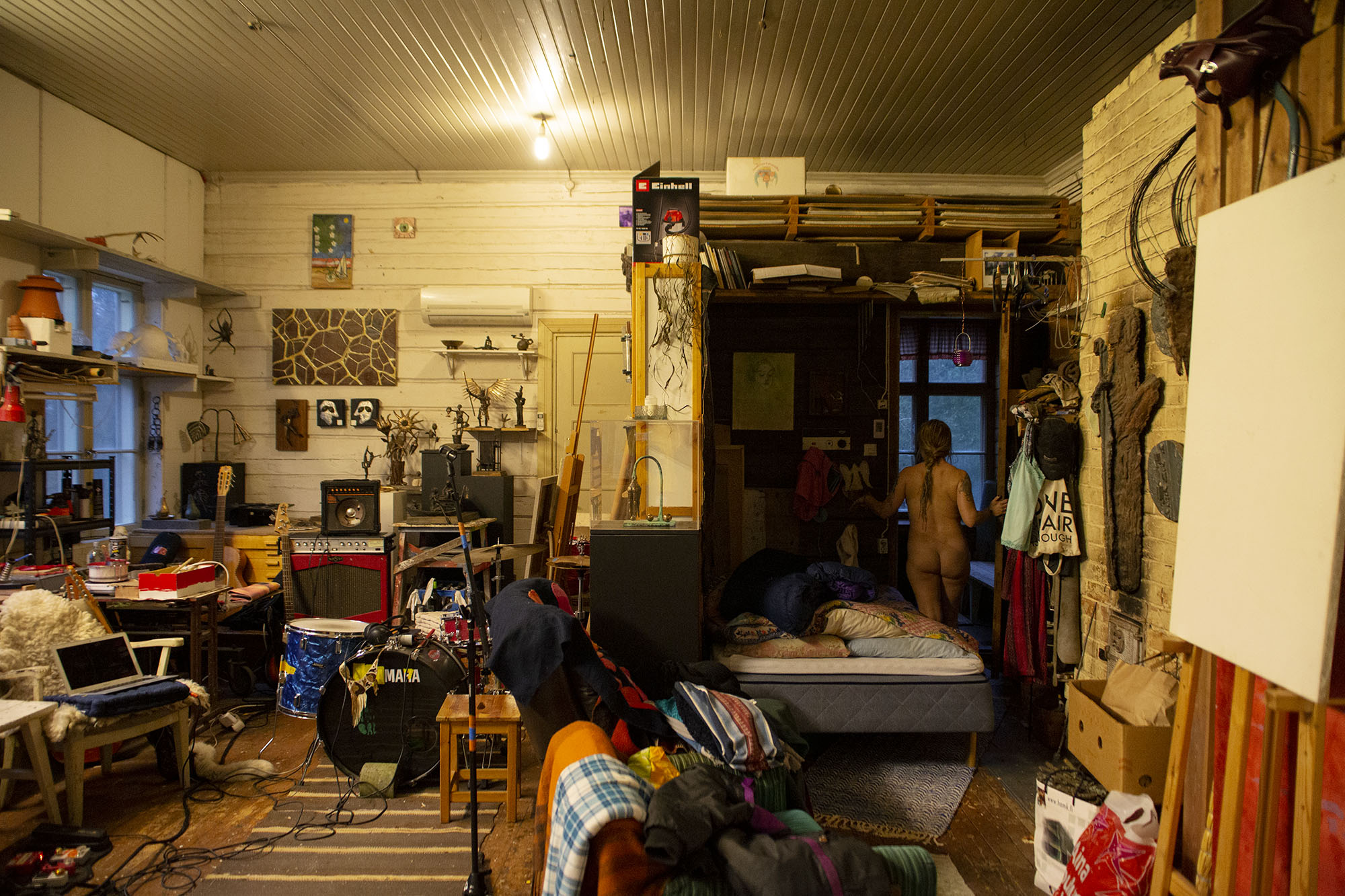 Huone jossa paljon tavaraa ja nainen menossa suihkuun pylly paljaana