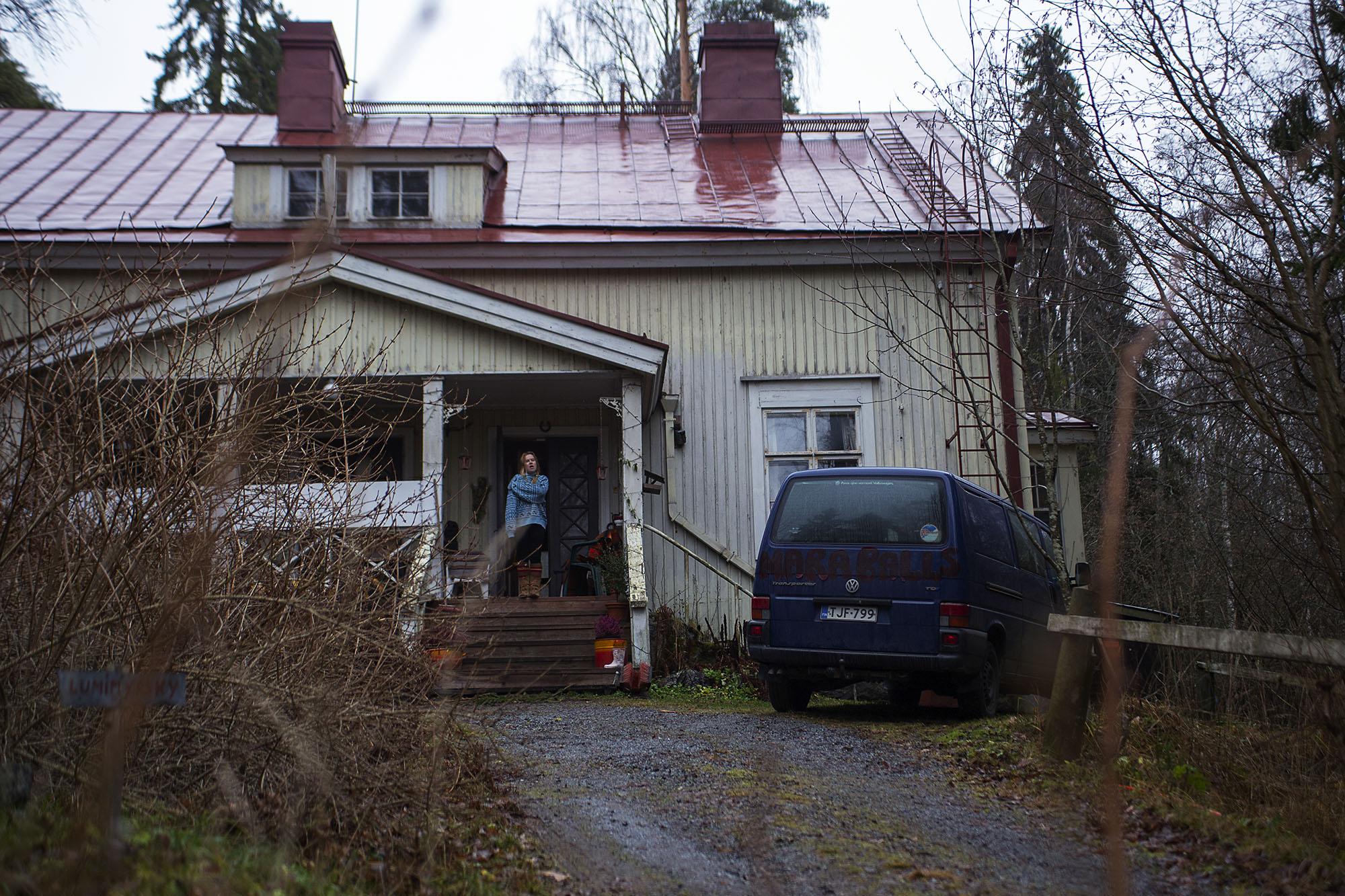 Vanha talo harmaassa syysmaisemassa, nainen haukottelee portailla. Talon edessä pakettiauto parkissa.