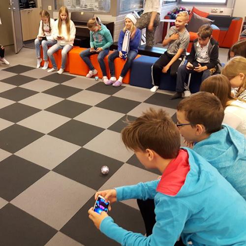Kuva KAKS10 56 -oppimisympäristöstä. Kuvassa oppilaita ohjaamassa Sphero-robottipalloja avoimessa Katsomo-tilassa.