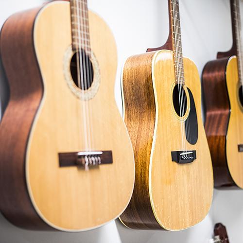 Kuvassa on rivistö akustisia kitaroita.