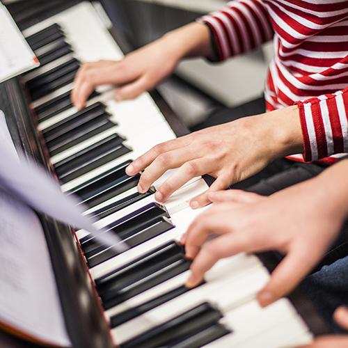 Kuvassa on kaksi oppilasta soittamassa pianoa nelikätisesti.