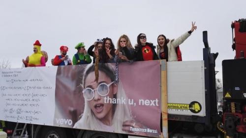 lukion abiturientteja päivän puvuissaan kuorma-auton lavalla
