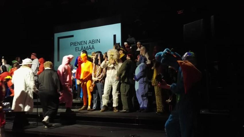 lukion abiturientteja päivän puvuissaan lavalla