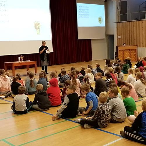Kuvassa on alakoulun oppilaita salin lattialla istuen seuraamassa adventtihartauden ohjelmaa.