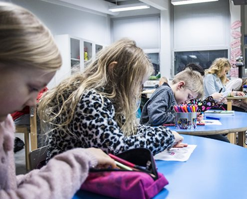 Viisi alakoulun oppilasta ovat oppitunnilla värittämässä monisteen tehtävää.