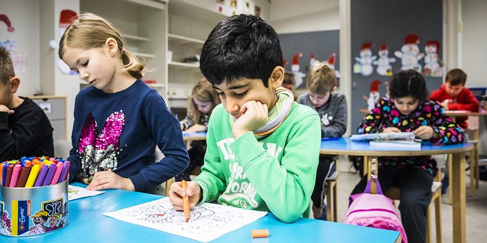 Kaksi alakoulun oppilasta ovat oppitunnilla värittämässä monisteen tehtävää.