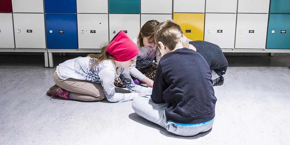 Neljä alakoulun pikkuoppilasta ovat käytävän lattialla piirissä istuen tekemässä yhteistä tehtävää.