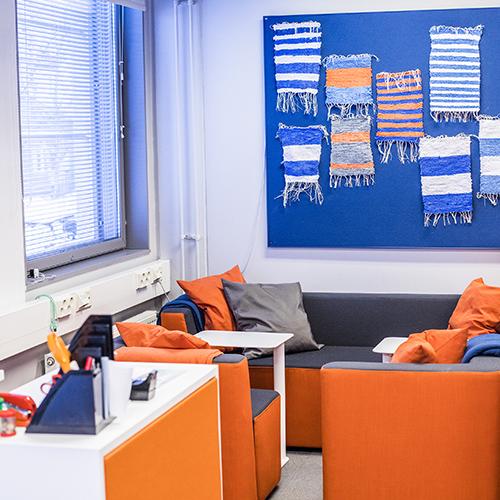 Kuva KAKS10 56 -oppimisympäristön nurkkauksesta, jossa on oranssit nojatuolit ja sohva tyynyineen.
