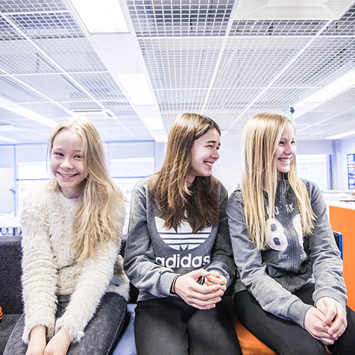 Lähikuvassa kolme kuudesluokkalaista tyttöä hymyilevät iloisena Kaksion katsomossa.