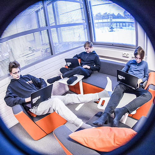 Kuvassa kolme kuudesluokkalaista poikaa ovat rennosti istuskellen Kaksion sohvanurkkauksessa tekemässä tehtäviään tietokoneilla.