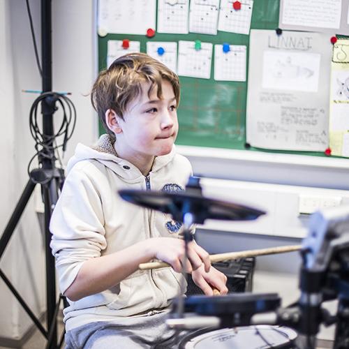 Kuvassa alakoulun poika on soittamassa rumpuja keskittyneesti.