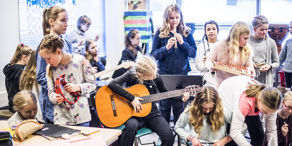 Kuvassa on kahdeksan alakoulun musiikkiluokan oppilasta soittamassa eri soittimia, kitaraa, nokkahuolua, ksylofonia ja rumpuja.