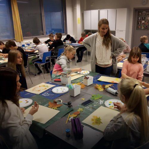 Nuori nainen, joka on opetusharjoittelussa, katsoo oppilaiden työskentelyä, kun he maalaavat värikkäitä syksyn lehtiä paperille.