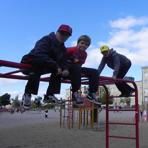 Kuvassa kolme poikaa on pari metriä korkeassa kiipeilytelineessä alakoulun pihassa.