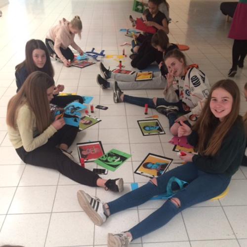 Kuvassa on joukko alakoulun oppilaita viimeistelemässä tekemiään värikkäitä kasvokuvia pientä taidenäyttelyä varten.