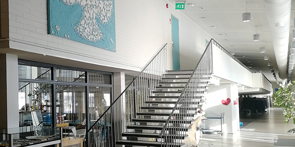 Valoinen kuva Norssin aulasta, jossa näkyy raput, lasiseinää, käytävää ja myös suuri sinertävä oppilaiden tekemä maalaus, jossa on iso valkoinen kyyhkysen hahmo.