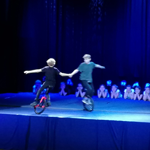 Kuvassa on oppilaiden sirkusesitys yksipyöräisillä polkupyörillä itsenäisyysjuhlassa.