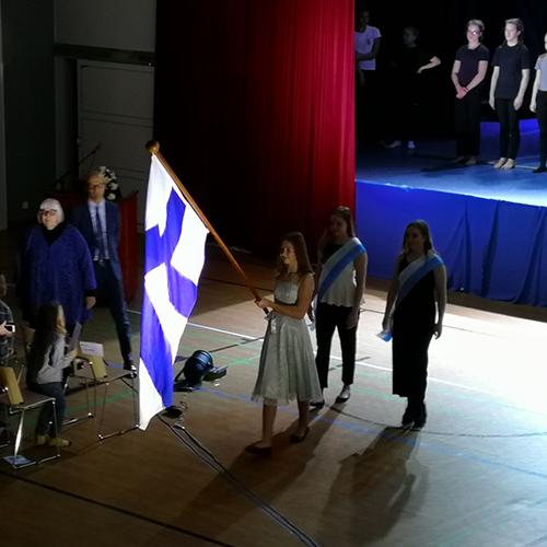 Kuvassa on Suomen lippu ja oppilaiden lippusaattue Suomi 100-itsenäisyysjuhlassa.