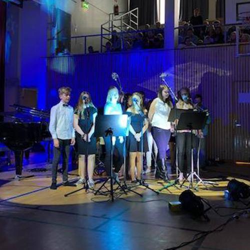 Kuvassa on ryhmä yläkoulun oppilaita laulamassa itsenäisyysjuhlassa koulun juhlasalissa.