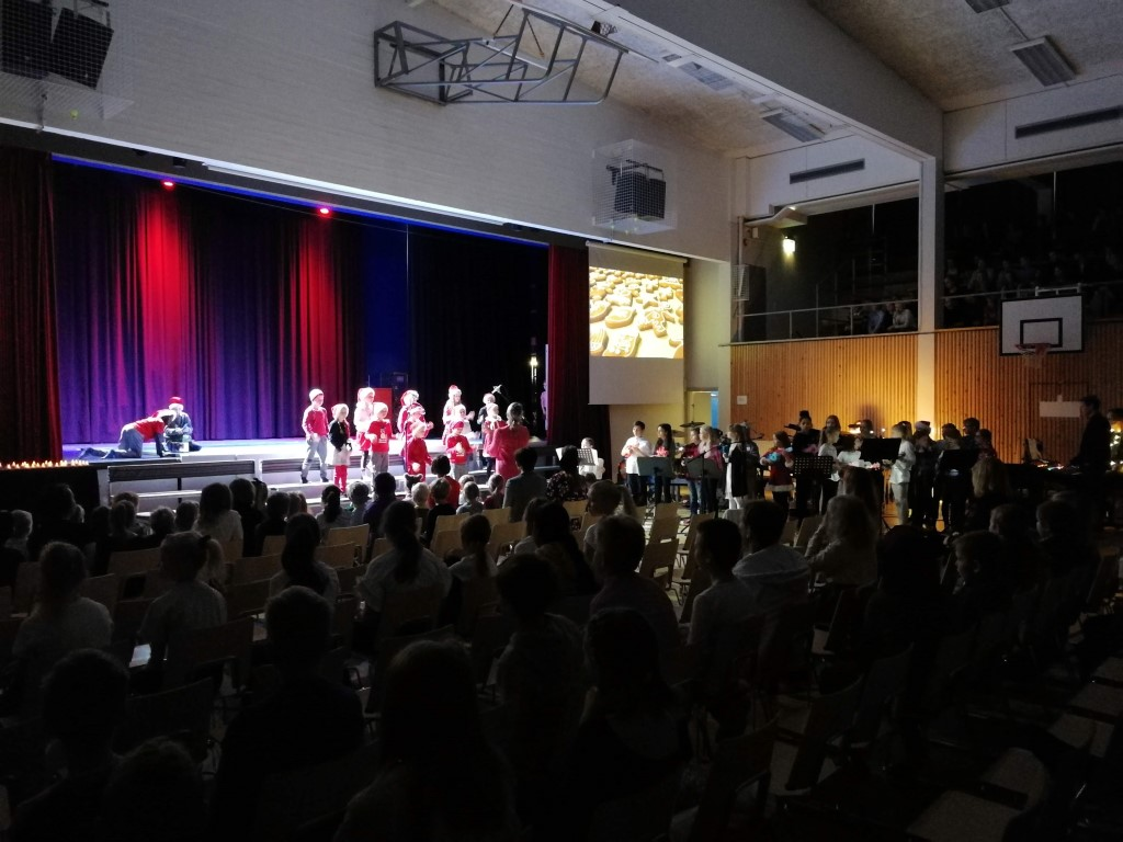 Oppilaiden esitys joulujuhlassa - pienet tontut laulavat ja näyttelevät.