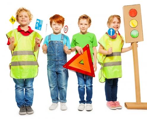 Kuvassa on poseeraamassa neljä iloista pikkulasta heijastinliivien ja liikennemerkkien kanssa.