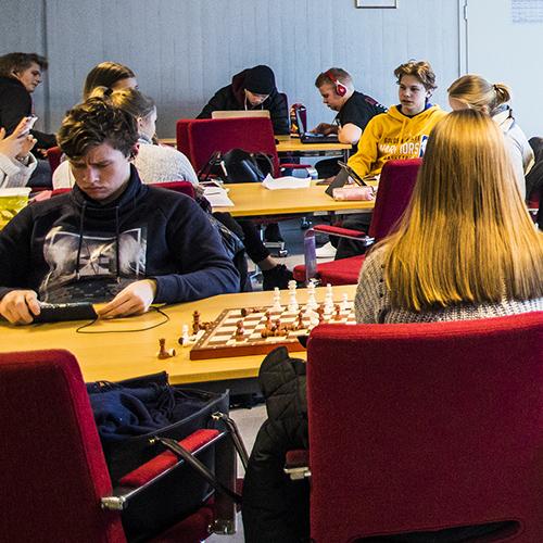 Kuva lukion opiskelijoista, jotka viettävät taukoa mobiililaitteiden, tietokoneiden ja shakki-peln parissa.