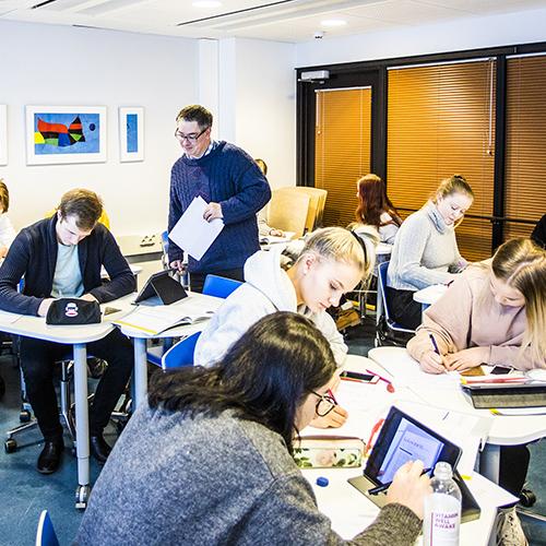 Kuva lukion oppitunnilta, jossa opiskelijat työskentelevät tietokoneiden, oppikirjojen ja tehtävien parissa.