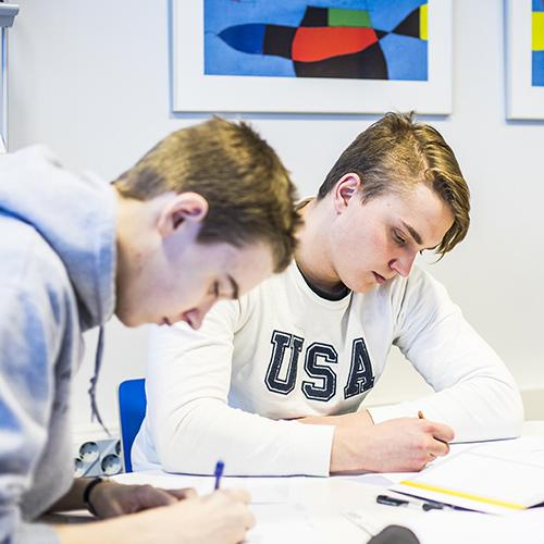 Kuva lukion oppitunnilta, jossa opiskelijat työskentelevät oppikirjojen ja tehtävien parissa.