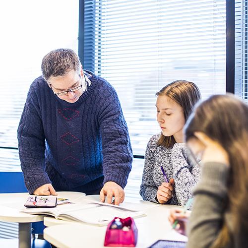 Äidinkielen opettaja Harri Mustonen on opastamassa paria lukiolaistyttöä oppitunnilla pöydän ääressä.