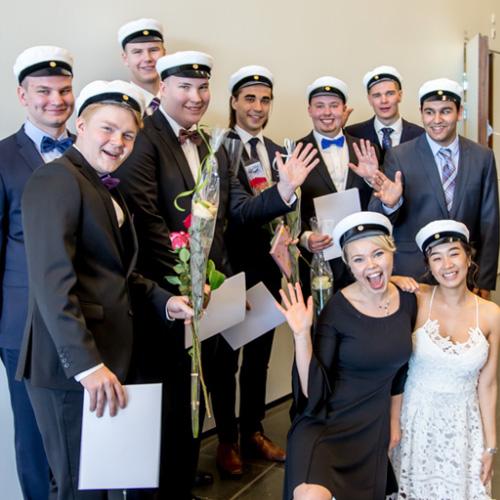 Kuvassa poseeraa valkolakit päässään hymyillen 10 uutta ylioppilasta.