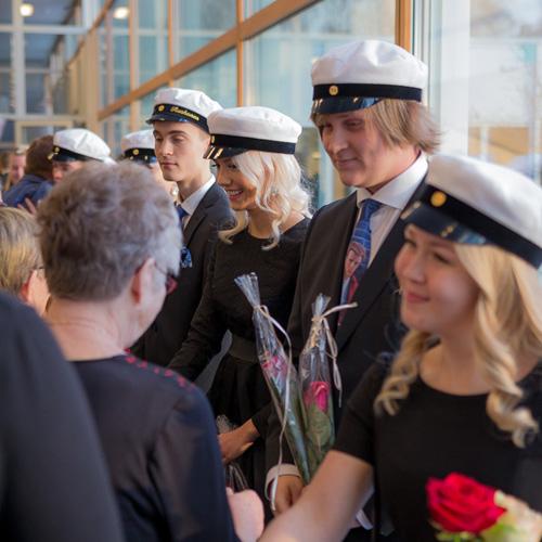 Kuvassa on muutamia uusia ylioppilaita vastaanottamassa omaisten onnitteluita lukion kevätjuhlan jälkeen.