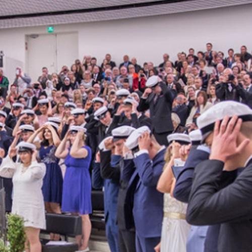 Kuvassa kymmenet uudet ylioppilaat laittavat kevätjuhlassa valkolakkeja päähänsä.