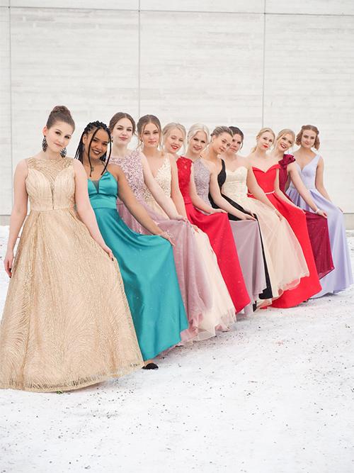 Kuvassa on 11 opiskelijaneitokaista värikkäissä juhlamekoissaan poseeraamassa vanhojen päivän juhlassa.