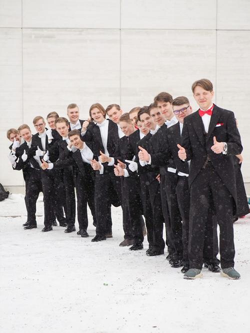 Kuvassa on 17 nuorta miestä tummissa puvuissaan vanhojen päivän juhlissa poseeraamassa ja näyttämässä peukaloitaan ylöspäin.