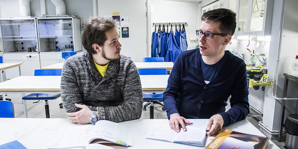 Kuvassa kaksi miestä istuvat vierekkäin ja oppikirjat ovat auki pöydällä, kun lehtori Juha Järvinen on ohjaamassa opiskelijaa.