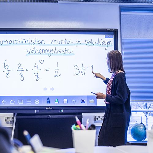 Nuori opetusharjoittelijanainen tekee älyteululle esimerkkiä murtolukujen laventamisesta.