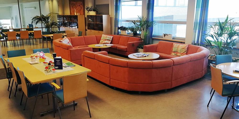 Kuva Norssin henkilöstöhuoneesta, jossa on suuret oranssit sohvat, pöytiä ja irtotuoleja sekä kirjahyllyjä.