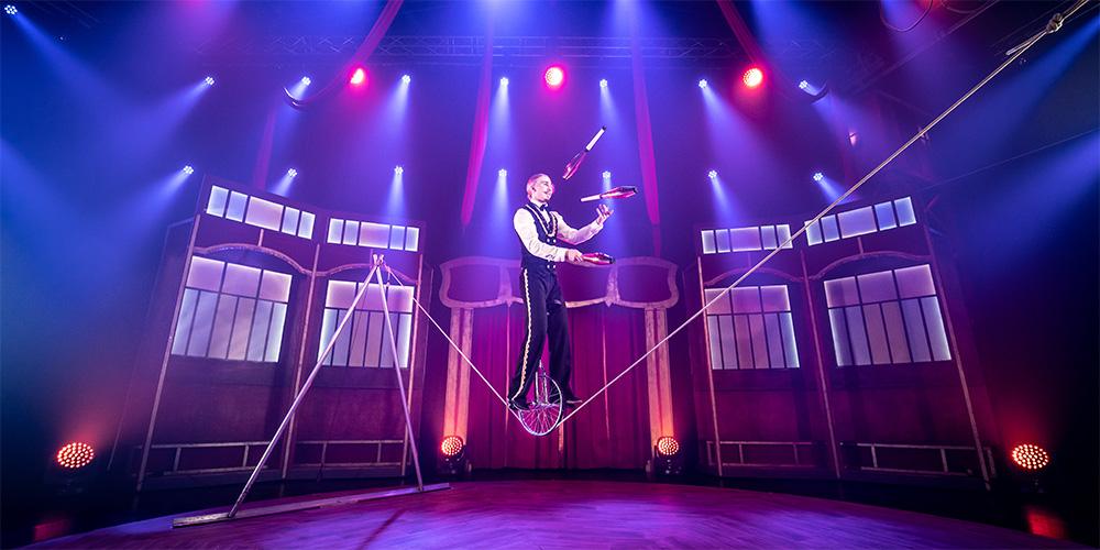 Kuvassa mies tasapainoilee yksipyöräisellä köyden päällä ja heittää samalla keiloja ilmaan.