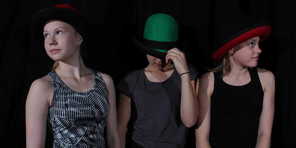 Sirkus-kuvassa on läheltä kuvattuna kolme oppilasta, kahdella punainen ja yhdellä vihreä esiintymishattu päässään.