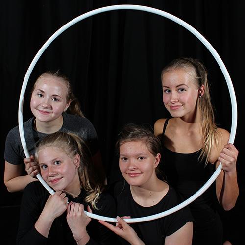 Sirkus-kuvassa on neljä tyttöä poseeraamassa hymyillen ja vanteen sisältä kurkiestaen.
