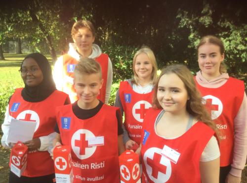 Kuvassa Nälkäpäiväkeräystä toimittavat kuusi yläkoulun oppilasta keräyslippaiden ja punaisen ristin liivien kanssa.