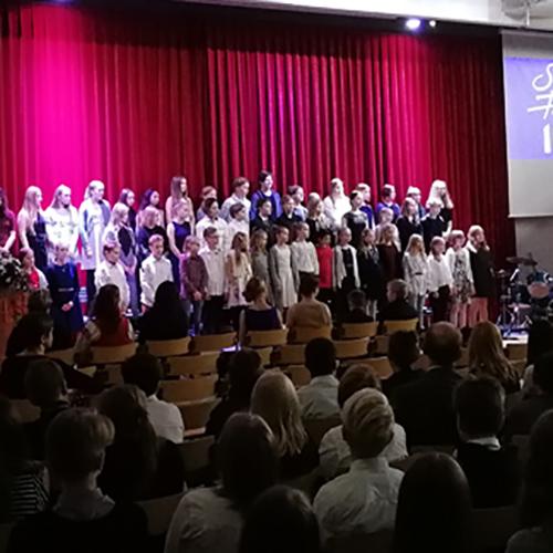 Kuva Norssin Suomi 100 -itsenäisyysjuhlasta. Oppilaitten kuoro on lavalla esiintymässä.