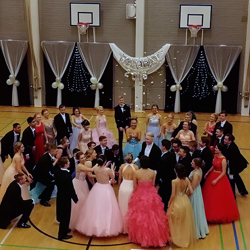 Kuva on vanhojen tanssiesityksestä Norssin juhlasalista, jossa opiskelijat ovat tiiviissä piirissä juhla-asuissaan.