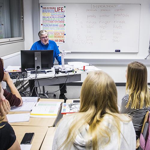 Kuvassa yläkoulun ruotsin tunnilla miesopettaja on luokan edessä tietokoneellaan ja takaa päin kuvatut oppilaat seuraavat opetusta.