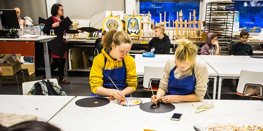 Kuvassa kuvataiteen tunnilta on oppilaita pöydän ääressä siveltimillä maalaamassa. Esiliinat on puettu päälle suojaamaan omia vaatteita.