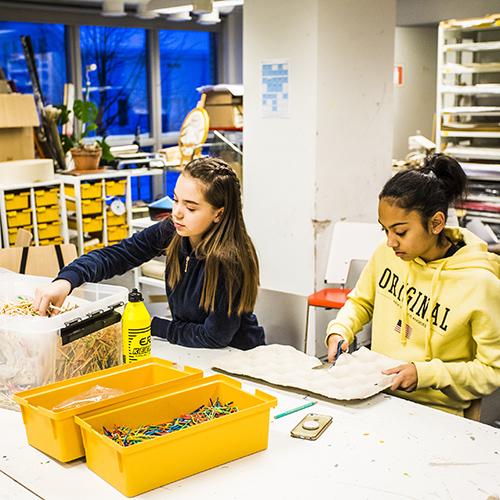 Kuvassa kuvataiteen tunnilta on oppilaita pöydän ääressä aloittelemassa rakentelutehtävää.
