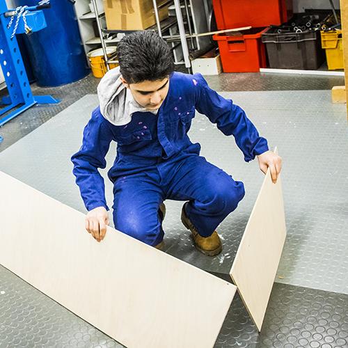 Kuvassa teknisen käsityön tunnilta on poika suunnittelemassa vanerilevyjen kanssa muotoa tulevalle työlleen.