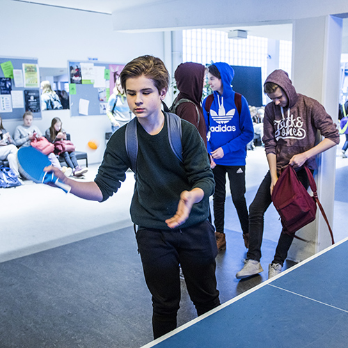 Kuvassa on poika pelaamassa pingistä koulun aulassa välitunnilla.